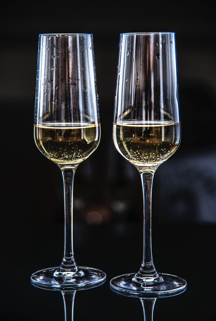 two clear champagne glasses filled with yellow liquids